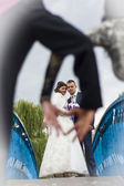The groom and the bride on walk in autumn park in a frame in the shape of hearts, made out of hand — Stock Photo