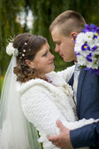 The groom and the bride on walk in autumn park kissing — Stock Photo