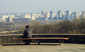 Lonely grandmother sits himself analysis looks at the city bench — Stock Photo