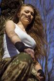 Beautiful young woman holding an automatic assault rifle — Stock Photo