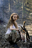 Beautiful young woman holding an automatic assault rifle — Stockfoto