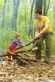 Daddy little girl helps to kindle a fire in the forest — Stock Photo
