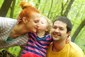 Happy mother and father kissing their daughter in the park — Stock Photo