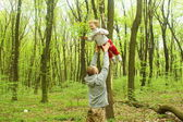 Man playing with baby girl tossing her up in the park — Stock Photo