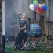 Stock Photo: Young sexy woman with balloons and baby carriage