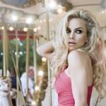 Fashion sexy model posing on carousel — Stock Photo