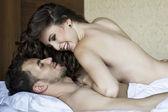 Los amantes de la joven tumbado en la cama — Foto de Stock