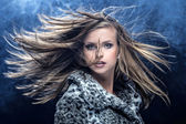 Portrait of pretty young woman flinging long blonde hair — Stock Photo