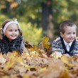 Little boy and girl laying down on grass — Foto Stock