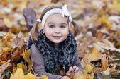 Adorable little girl with autumn leaves in the beauty park — Stock Photo