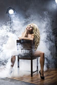 Sexy blonde woman with photo light flash — Stock Photo