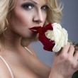 Close-up portrait of beautiful blonde woman with red - white ros — Stock Photo #18930663