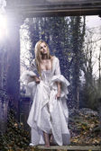 Gorgeous blonde beauty in a old-fashioned dress in a forest — Stock Photo