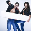 Fashionable happy couple holding white board — Stock Photo