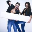 Fashionable happy couple holding white board — Stock Photo
