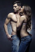Linda jovem casal sorridente no amor abraçando indoor — Foto Stock