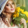 Stock Photo: Beautiful womwith bouquet of sunflowers