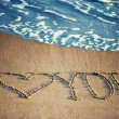 Stock Photo: I love you - written in the sand with a foamy wave underneath