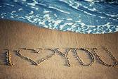 Ik hou van je - geschreven in het zand met een schuimend golf onder — Stockfoto