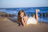 Happy beauty young woman lying on the beach — Stock Photo