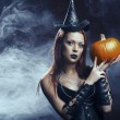 The serious girl is standing with the pumpkin in smoke — Stock Photo #32922831