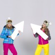 Two women in warm clothes with arrows — Stock Photo