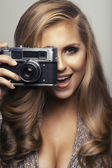 Smiling woman with camera — Stock Photo