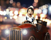 Smile child in wooden car in night on street — Stock Photo