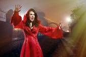 Elegant young witch in a red clothes cast magic spell in city — Stock Photo