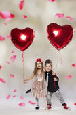 Happy kids with red heart balloon on a light background — Stock Photo