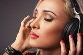 Escuchar música mujer atractiva a través de auriculares, ojos cerrados. — Foto de Stock