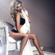 Portrait of beautiful young sexy woman sitting on chair — Stock Photo