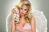 Young blond woman in angel costume with flower — Stock Photo