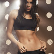 Young beautiful woman in fitness wear over modern background — Stock Photo