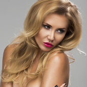 Young sexy blond woman without lingerie with pink lips posing on studio — Stock Photo