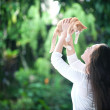 Asian woman raises a red cat in the park — Stock Photo
