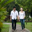 Asian couple holding hands walking on the park path — Stock Photo #20974895