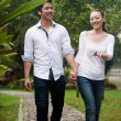 Asian couple holding hands walking on the park path — Stock Photo #20975025