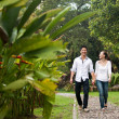 Asian couple holding hands walking on the park path — Stock Photo