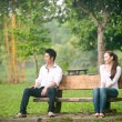 Asian young couple sitting away outdoors on a bench — Foto de Stock