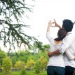 Happy asian couple in love showing heart with their fingers — Stock Photo