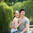 Asian couple sitting on embankment in the park — Stockfoto