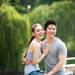 couple asiatique, assis sur le remblai dans le parc — Photo