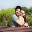 Asian couple hugging in the park — Stock Photo #20975261