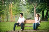 户外走坐在长凳上的亚洲年轻夫妇 — 图库照片