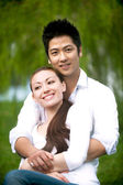 Asian couple hugging in the park — Stock Photo