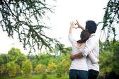 Feliz pareja asiática enamorada mostrando corazón con sus dedos — Foto de Stock