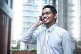 Smiling business man talking on cell phone — Stock Photo