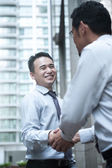 Smiling businessmen shaking hands — Stock Photo