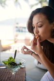 Asian girl tasting a finger food at a restaurant — Stock Photo